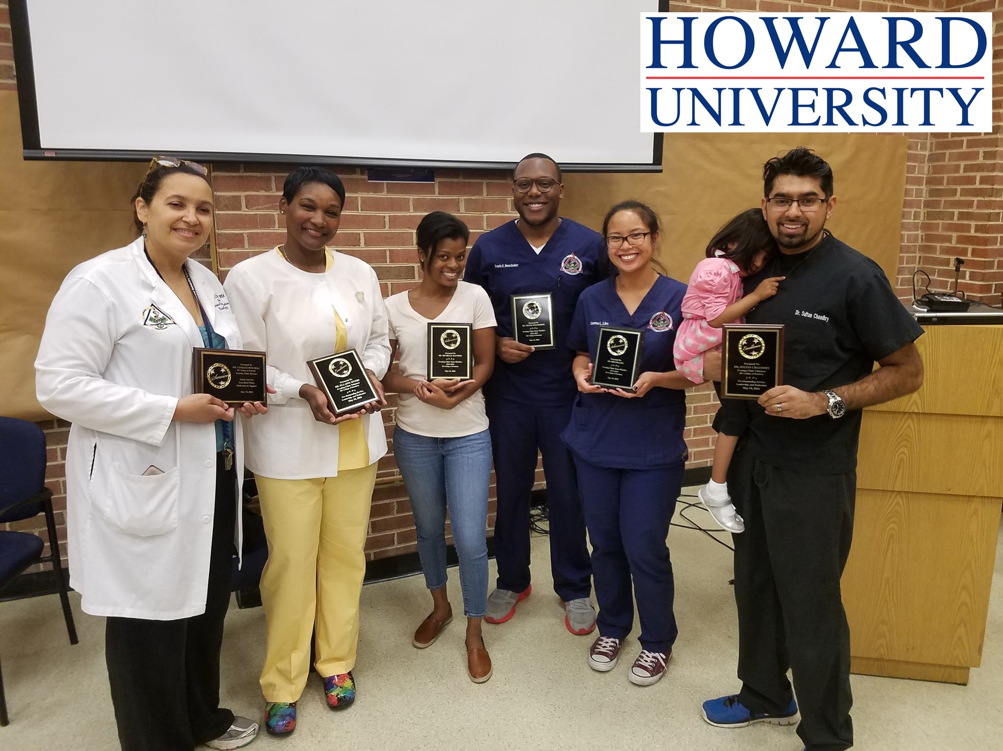 Dr. Chaudhry receives a teaching distinction at Howard University College of Dentistry alongside students and fellow faculty members.