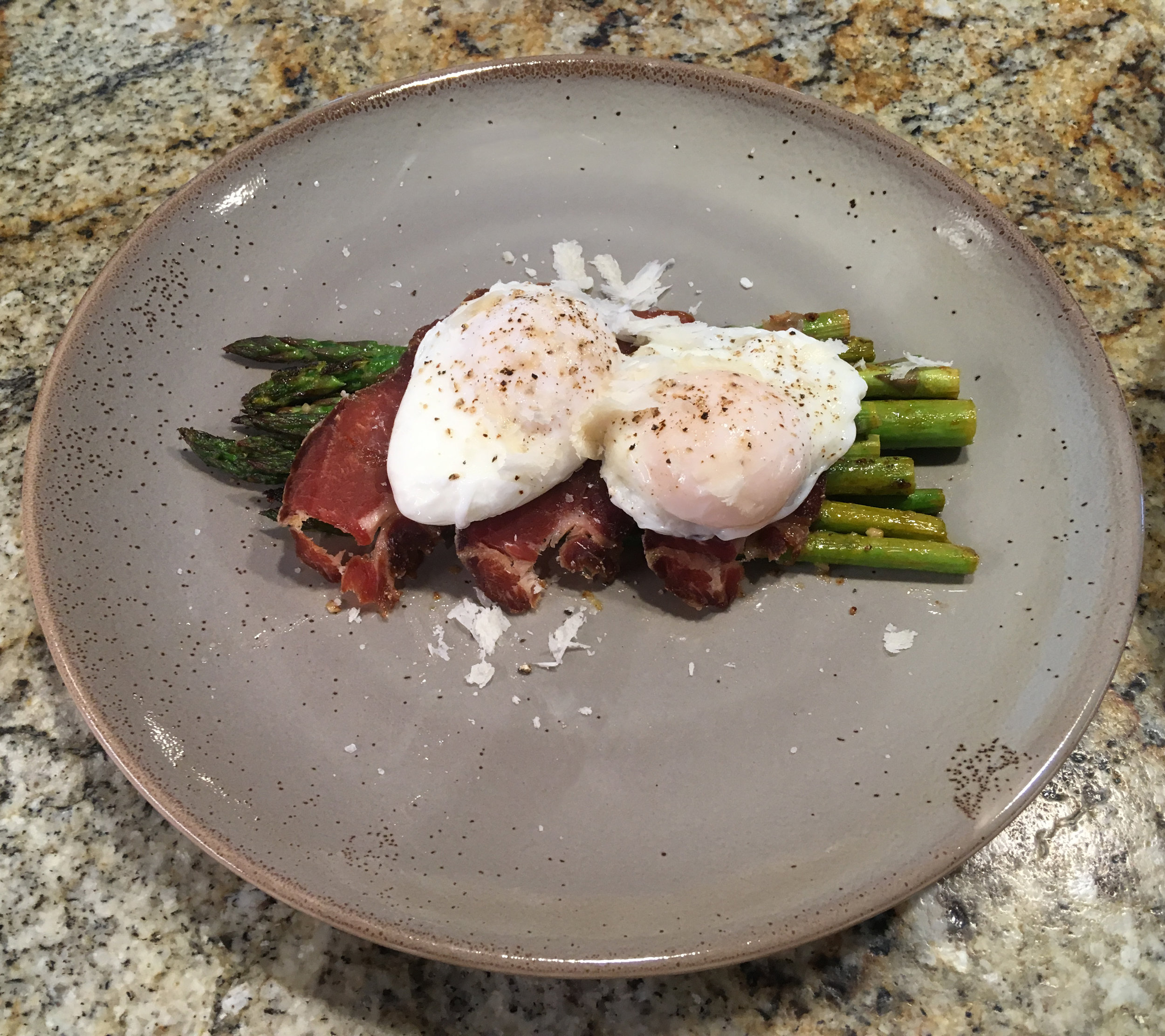Poached Eggs and Asparagus - Asparagus sauteed in oil, garlic, lemon zest, and lemon juice, topped with Mary Ann's homemade prosciutto and our farm fresh poached eggs, and finished with shaved parmesan.
