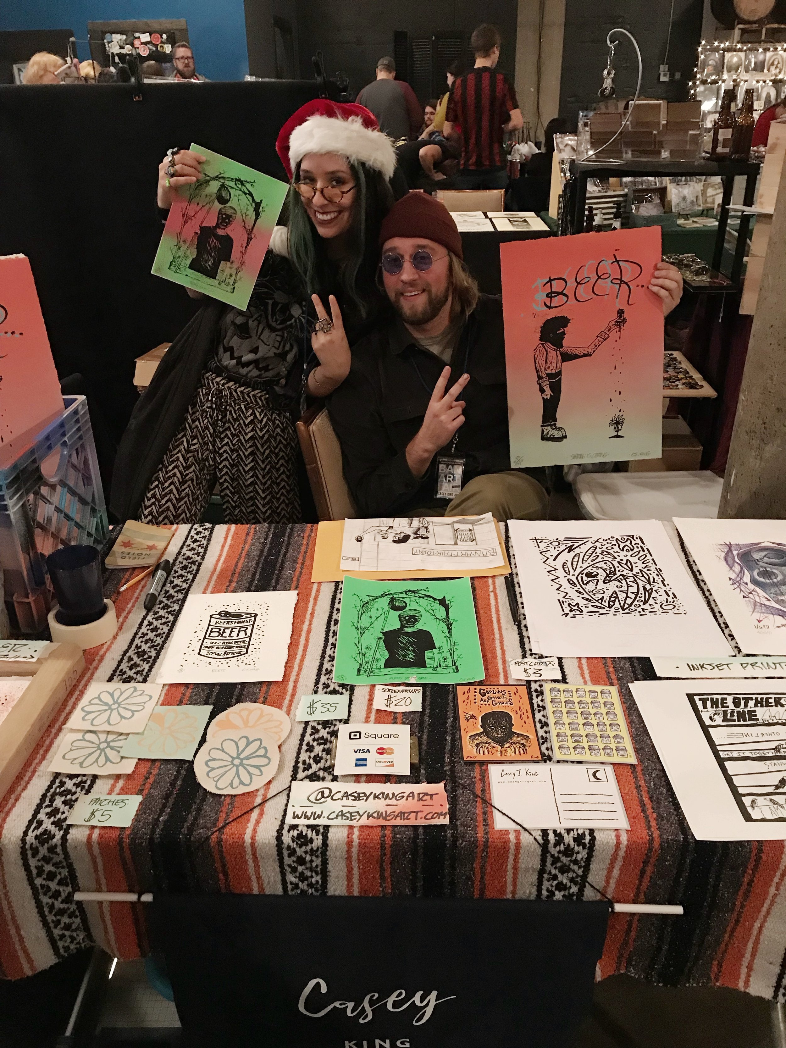 "Here is artist Sophia Rapata and I during Ban Art Fair 2017 at 18th Street Brewery. I'm holding a new screenprint I produced for the event. Sophia is holding a screenprint of my ""Mummy Youth"" graphic and being groovy as usual. My first big event setup as an independent artist and I managed to sell a few screenprints by the end of the day. To the folks who purchased something...thanks! You made my day.  - Casey"