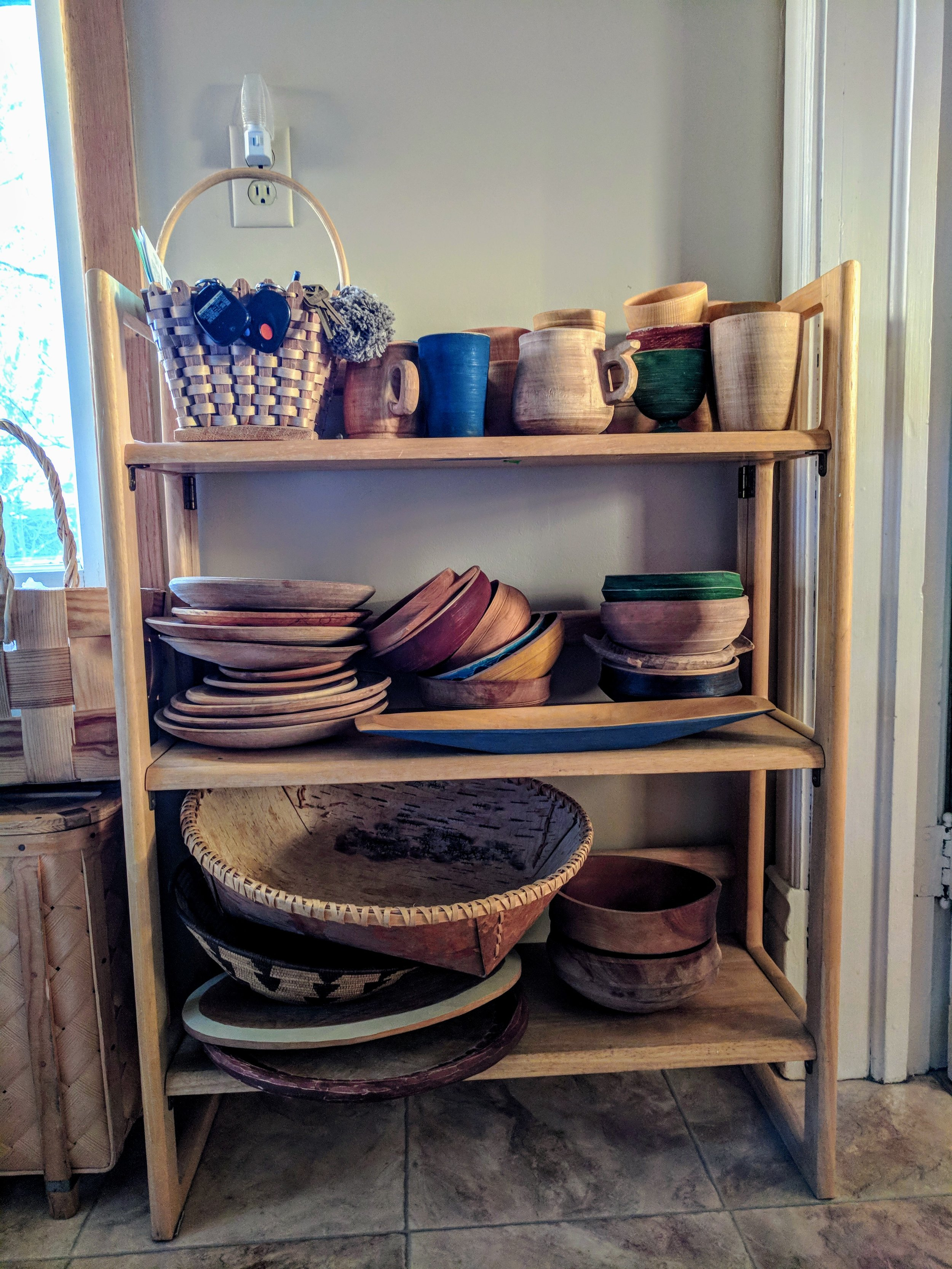 shelves with handmade wooden bowls plates and cups