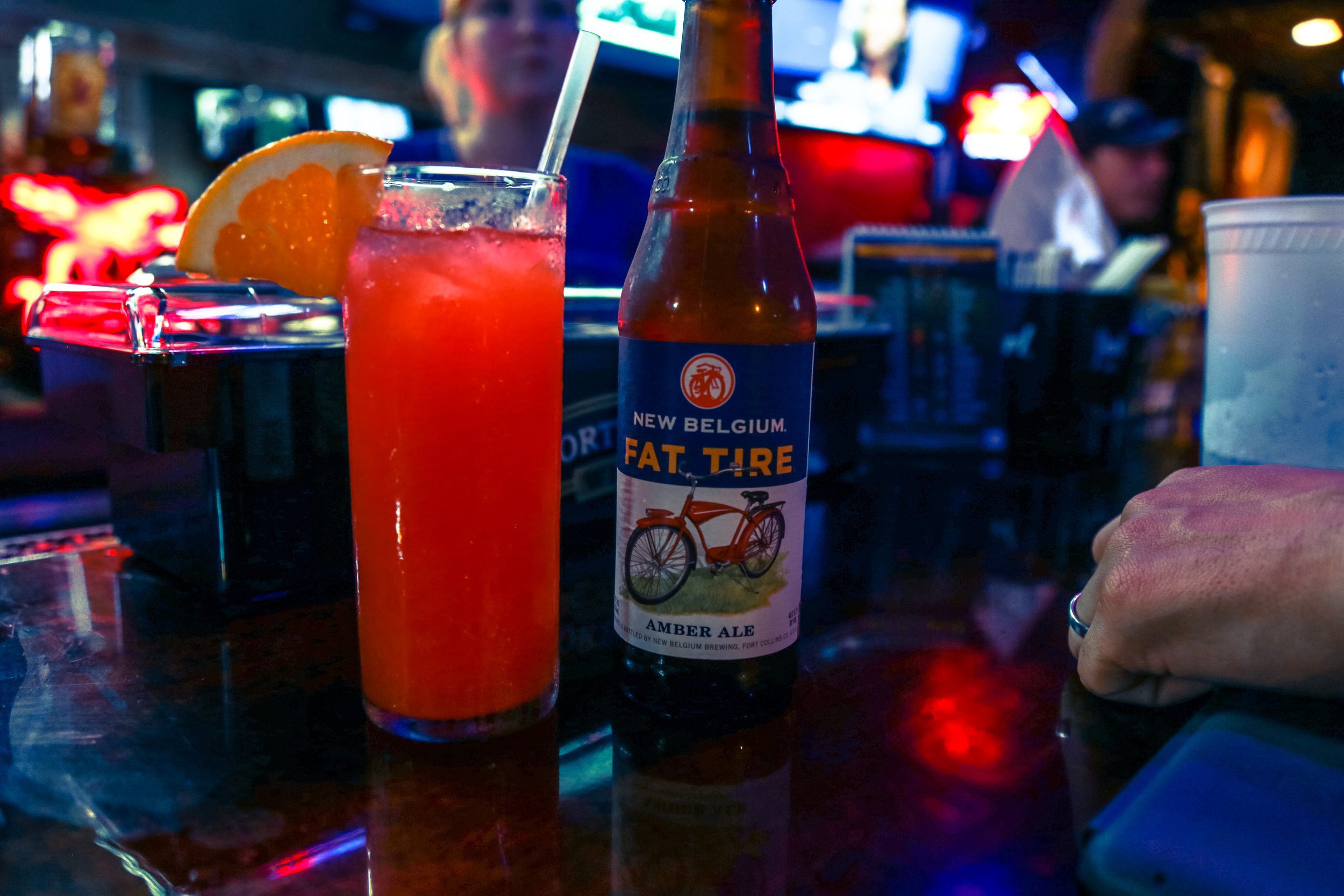 New Belgium Fat Tire Amber Ale sitting next to a mixed drink at sports bar American Sports Saloon in New Orleans, LA