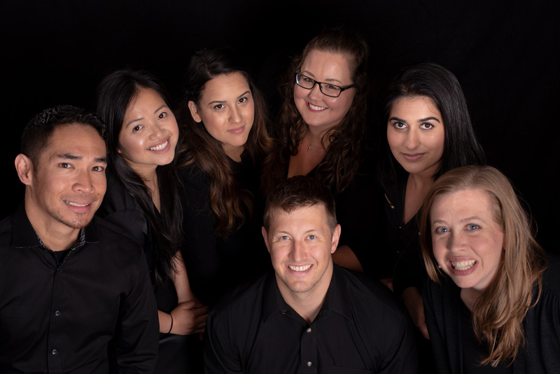 The Cedar Dental Group team smiling up in black shirts.