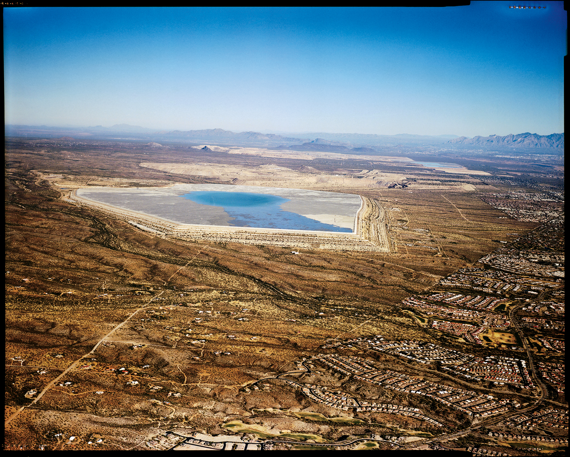 A tailings pond of waste materials left over after the copper-ore extraction process at the Sierrita Mine, near the Canoa Estates retirement community (center right). Copper mines, along with golf courses are significant contributors to water depletion in Arizona, which has been in a drought for over two decades.