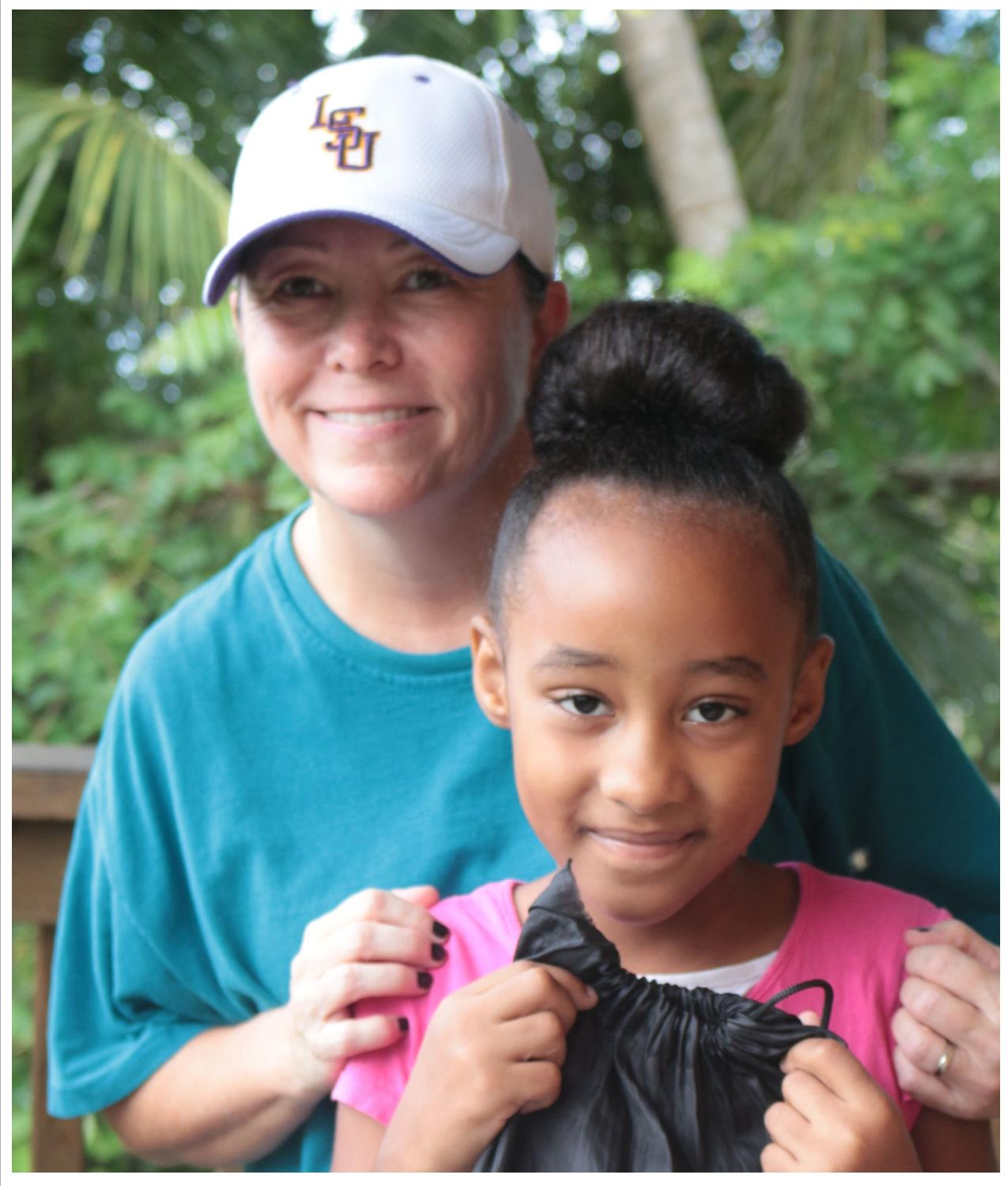 Our missionary, Robyn, with one of the children who receives a back pack of food each week