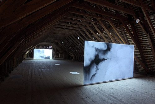 """Smoke'' (installation view, two-channel video, looped), by LISA OPPENHEIM"