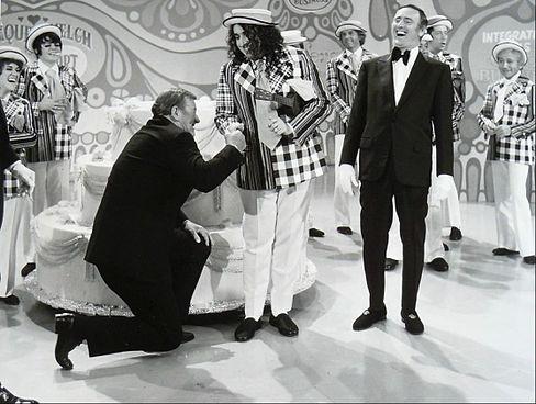 John Wayne and Tiny Tim helped  Laugh-In celebrate its 100th episode in 1971. Co-host Dan Rowan yucks it up in his tuxedo .