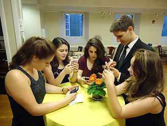 Young_people_texting_on_smartphones_using_thumbs.JPG