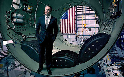 Elon Musk stands inside a rocket that is awaiting assembly.    -- SpaceX photo