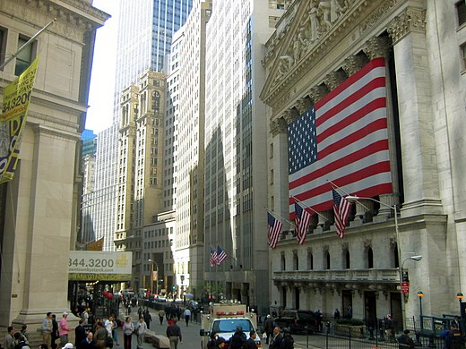 The epicenter of merger mania -- Wall Street, with the New York Stock Exchange draped with the flag.