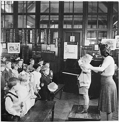 A teacher   helps a young pupil conduct an ''orchestra'' during a music lesson at St Joseph's Elementary School, in Upper Norwood, England., in 1943. The boy is using drumsticks or xylophone beaters to conduct the rest of the class, who are playing tambourines, triangles and cymbals .