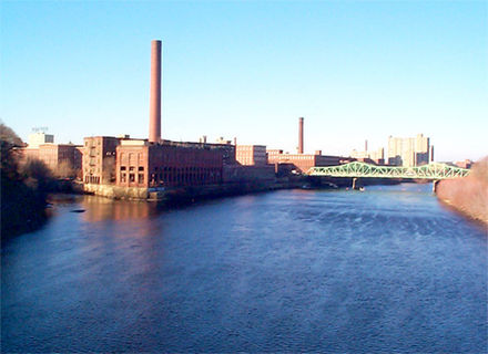 In Lowell, the Massachusetts Mill at the confluence of the  Merrimack  and  Concord  rivers; across the Cox Bridge are the Boott Mills.