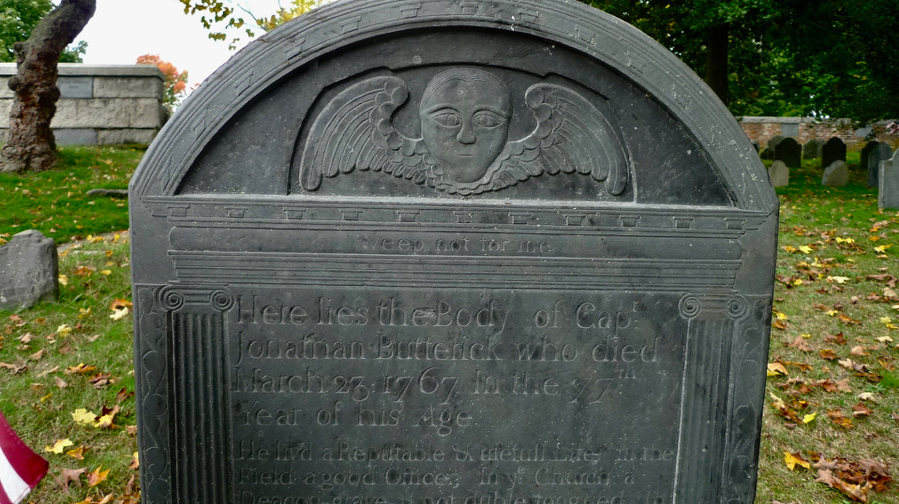 """Old Hill contains some classic and noted examples of New England stone carving: seraphim, death's heads and hourglasses that have run out of time. This is the resting place of Captain Jonathan Butterick (1690-1767). The grave says """"Weep not for me''."""