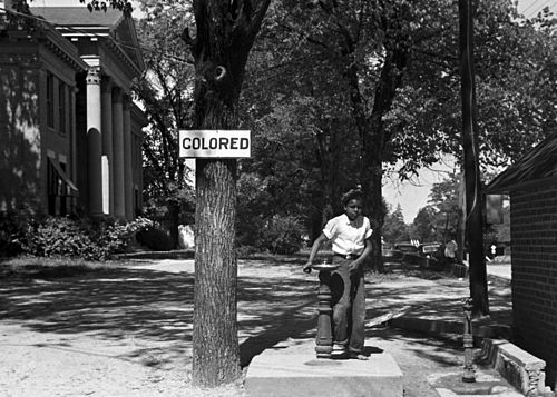 An    African-American    child at a segregated drinking fountain on a courthouse lawn in    North Carolina   , in 1938.