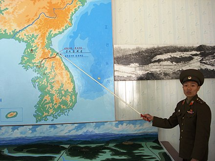 North Korean soldier points to the demilitarized zone between the two Koreas.