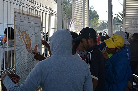 Migrants from Central America looking at maps for routes to the U.S. border