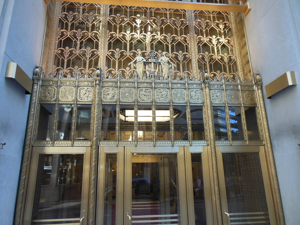 """The wonderfully ornate main entrance to the glorious United Shoe Machinery Building, at 160    Federal St   ., in the    Financial District    of    Boston   . The steel-frame skyscraper has 24 stories and a penthouse, and was built in 1929–1930 and designed by George W. Fuller and    Parker, Thomas & Rice    to serve as    United Shoe Machinery Corp   .'s headquarters.    It is one of Boston's finest Art Deco buildings, including an elaborately decorated lobby. The long-dead United United Shoe Machinery (in Boston often just called """"Shoe'') was a huge manufacturer of a wide range of industrial goods, including many things for the defense industry. At one time it controlled 98 percent of the nation's shoe-machinery business and much of that business abroad, too. Of course the American shoe business was based in New England for many years.    Below see the tower with its famous gold top."""