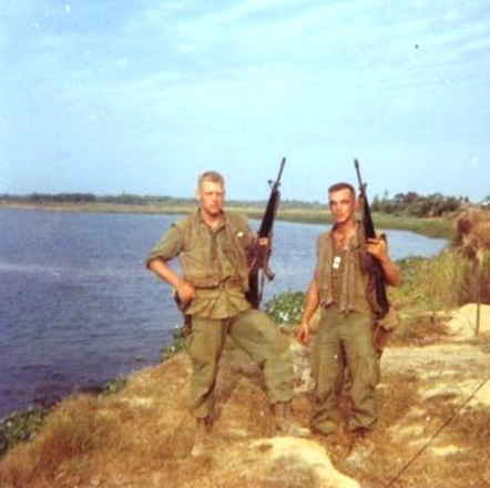 """Mr. Mallon is at the left, with the M-16 and side arm. He wrote that the Marine at the right """"had taken a couple of rounds in his pelvis and had his guts in a bag the next time we met, in St. Albans Naval Hospital (in New York). He weighed about 90 pounds and looked like a skeleton. I can't remember his name but he was eventually healed, gained some weight and was retired.''"""