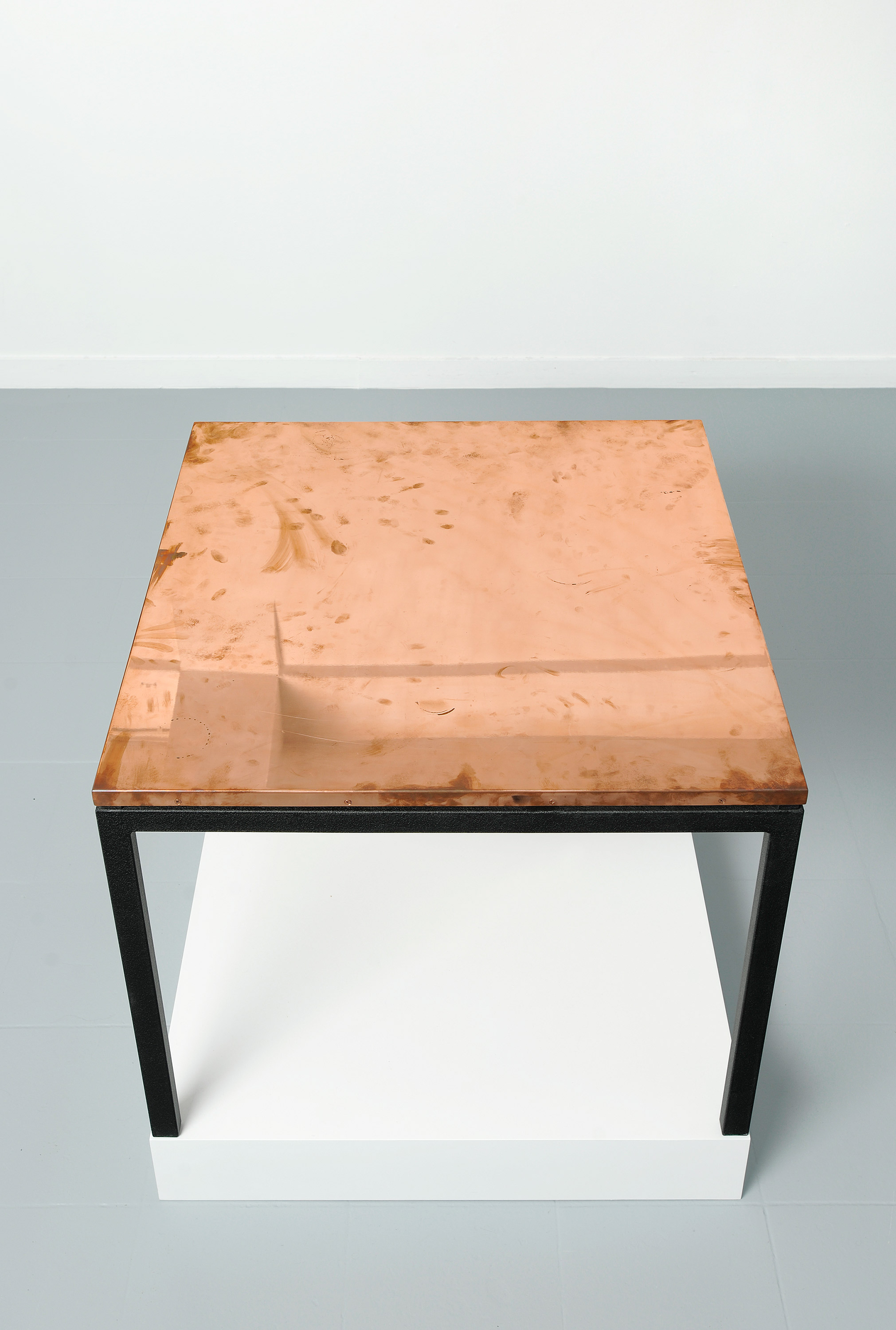 Copper Surrogate (Table: designed by Charlotte Perriand and Le Corbusier, 1959; Galerie Rodolphe Janssen, Brussels, Belgium, August 10th–September 2nd, 2011)    2011   Polished copper table top and powder-coat steel  Table: 33 5/8 x 33 5/8 x 1 inches   Surrogates (Tabletop and Desktop), 2008–
