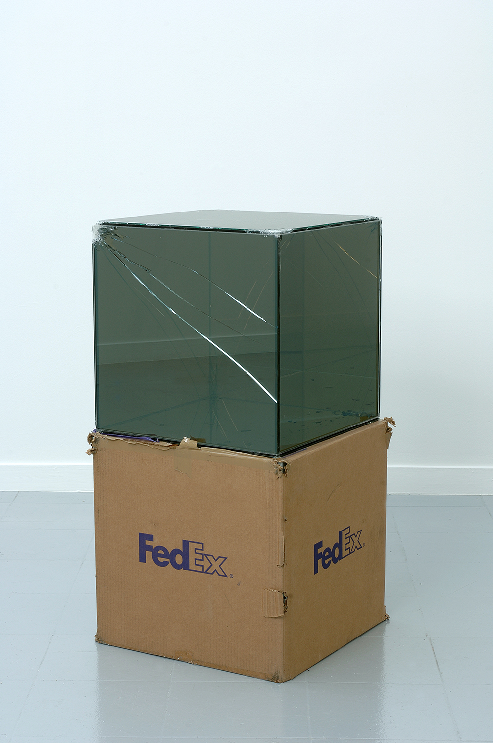 FedEx® Large Kraft Box  © 2005 FEDEX 330508 REV 10/05 SSCC, International Priority, Los Angeles–Brussels trk#865282057953, October 27–30, 2008, International Priority, Brussels–Los Angeles trk#866071746385, December 8–9, 2008    2008–   Laminated mirropane, FedEx shipping box, accrued FedEx shipping and tracking labels, silicone, metal, and tape  20 x 20 x 20 inches   FedEx Glass Works, 2007–