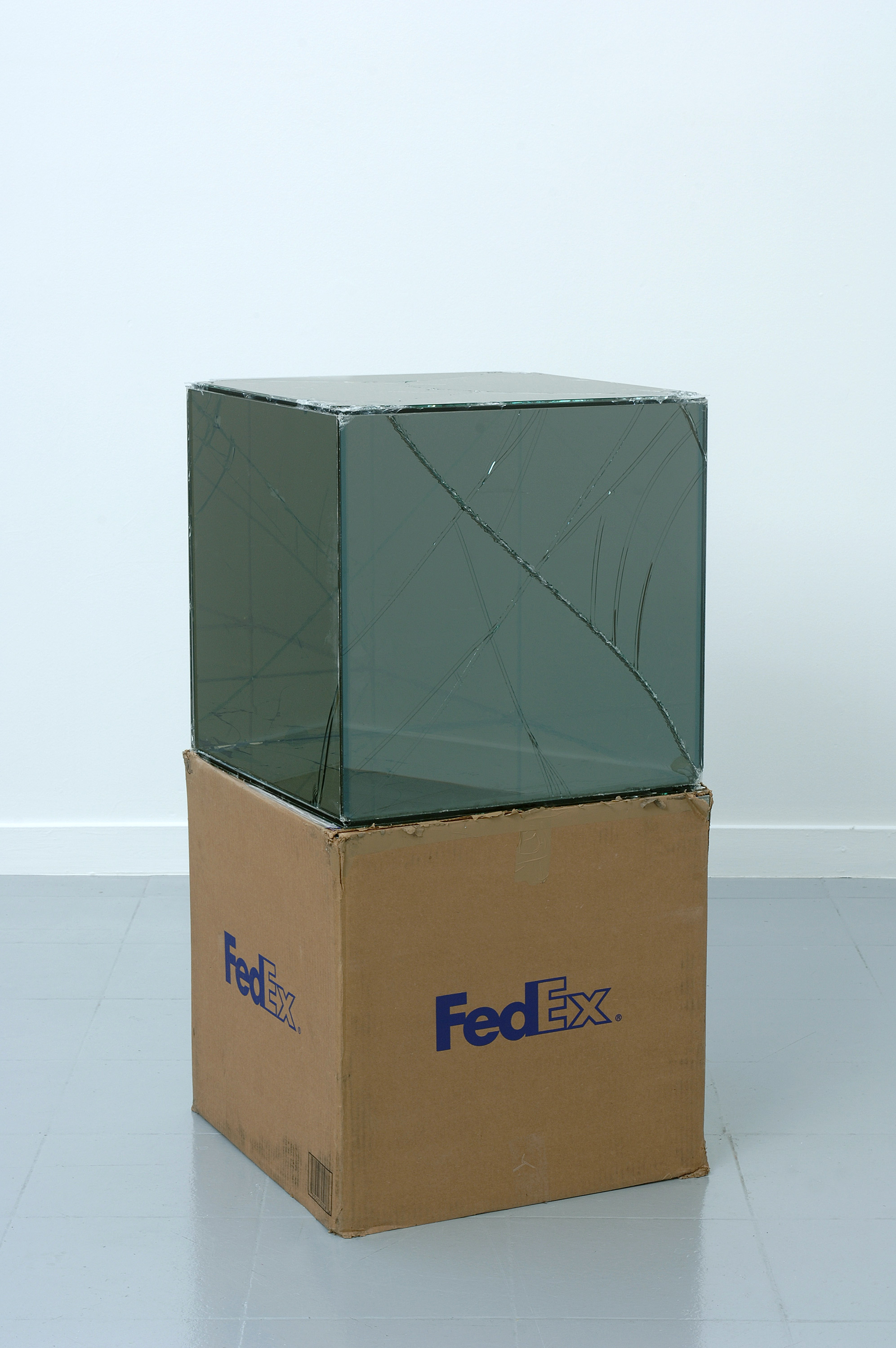 FedEx® Large Kraft Box  © 2005 FEDEX 330508 REV 10/05 SSCC, International Priority, Los Angeles–Brussels trk#865282057942, October 27–30, 2008    2008–   Laminated Mirropane, FedEx shipping box, accrued FedEx shipping and tracking labels, silicone, metal, and tape  20 x 20 x 20 inches   FedEx Glass Works, 2007–