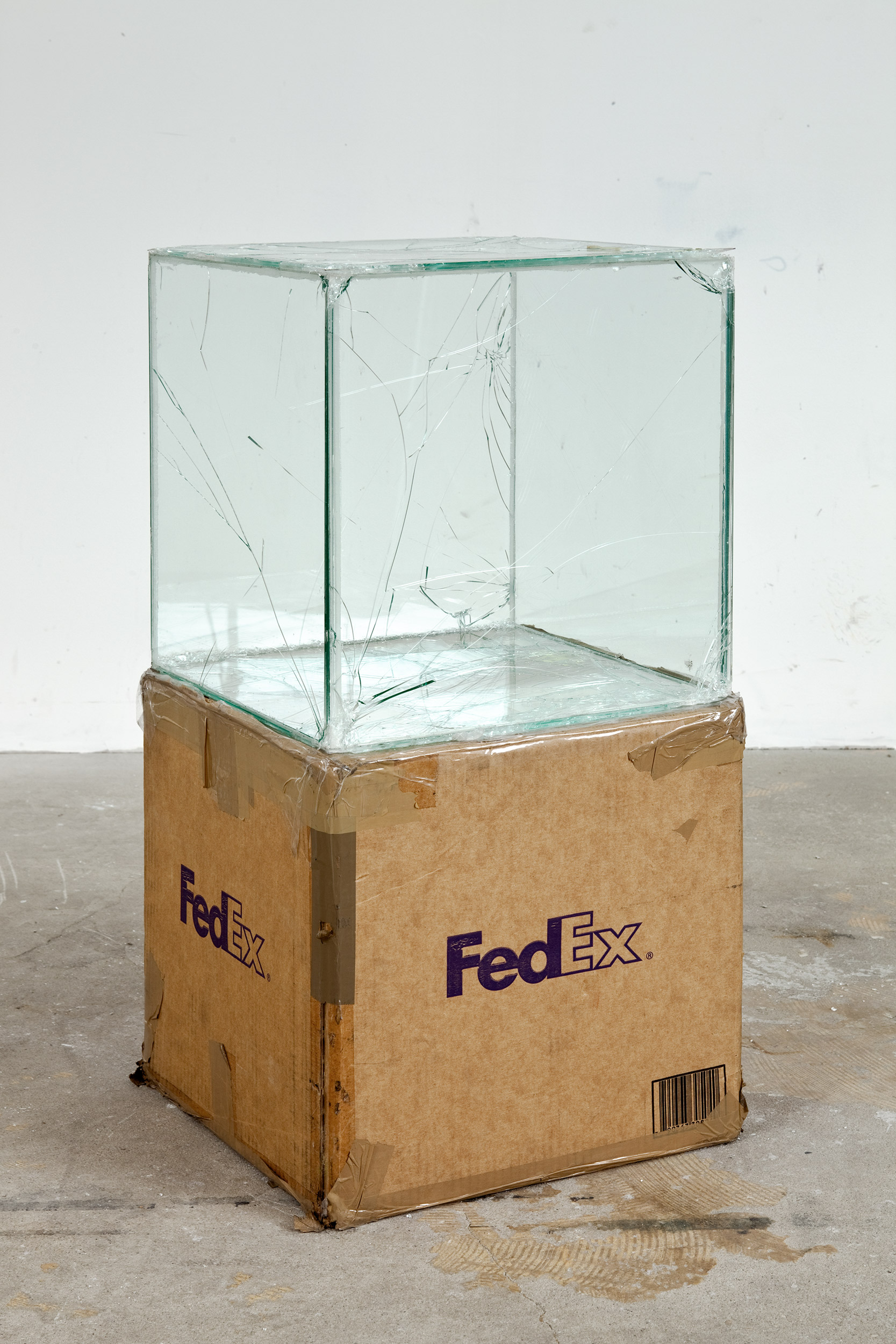 FedEx® Kraft Box  © 2005 FEDEX 330504 10/05 SSCC, Priority Overnight, Los Angeles-Miami trk#865344981299, October 29–30, 2008, Priority Overnight, Miami–Ann Arbor trk#861049125115, March 03–04, 2009, Standard Overnight, Ann Arbor–Los Angeles trk#868274625749, July 09–10, 2009, Standard Overnight, Los Angeles–San Francisco trk#878069766471, August 27–28, 2009, Standard Overnight, San Francisco–Los Angeles trk#870342520145, November 12–13, 2009, International Priority, Los Angeles–London trk#798269222978, April 10–12, 2012    2008–   Laminated glass, FedEx shipping box, accrued FedEx shipping and tracking labels, silicone, metal, tape  16 x 16 x 16 inches   Pulley, Cogwheels, Mirrors, and Windows, 2009