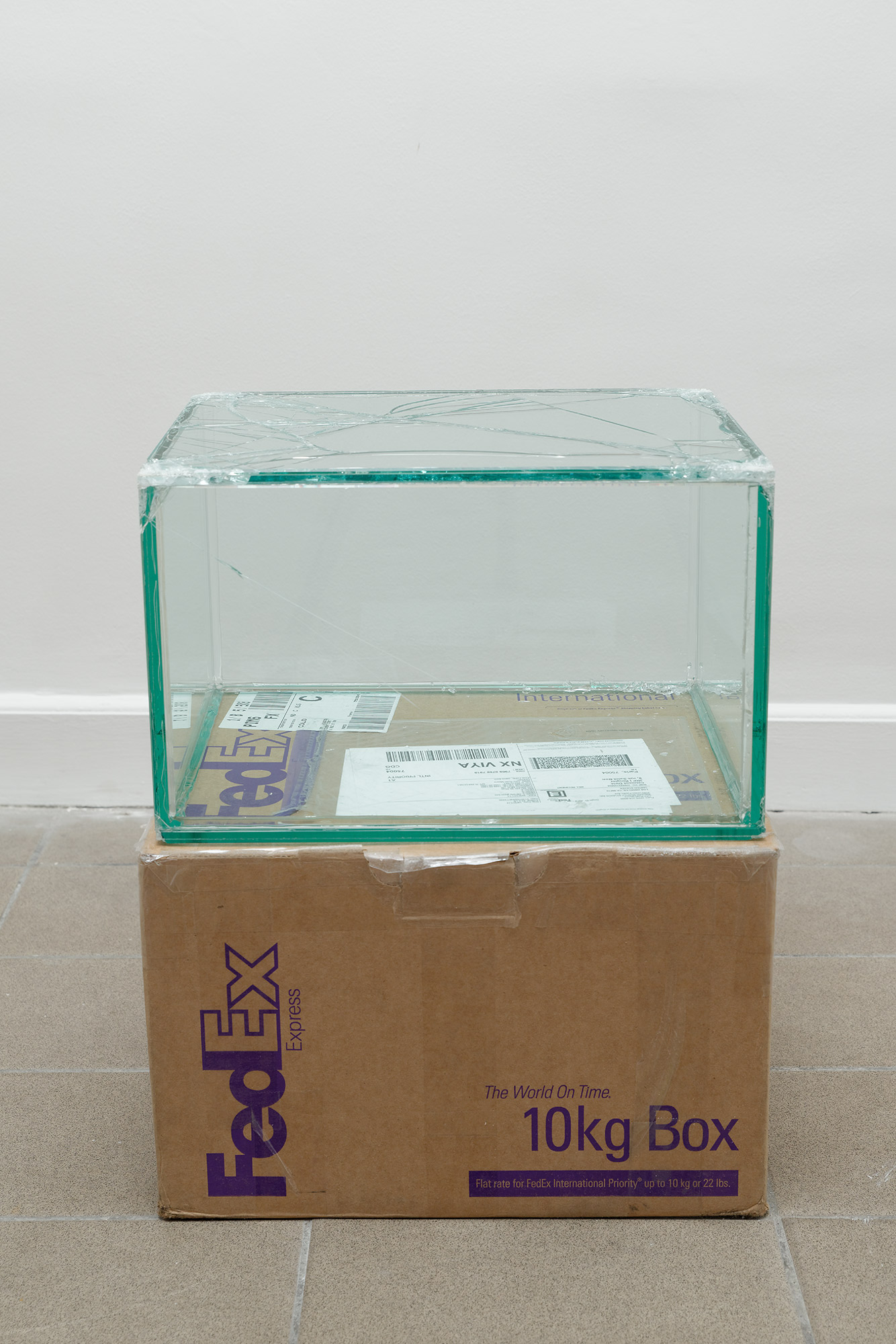 FedEx® 10kg Box  © 2006 FedEx 149801 REV 9/06 MP, International Priority, Los Angeles-Paris trk#796906988159, October 14-16, 2013   2013–  Laminated glass, FedEx shipping box, accrued FedEx shipping and tracking labels, silicone, metal, tape  10 1/2 x 16 1/4 x 13 1/4 inches   FedEx Glass Works, 2007–    8 rue Saint-Bon, 2013