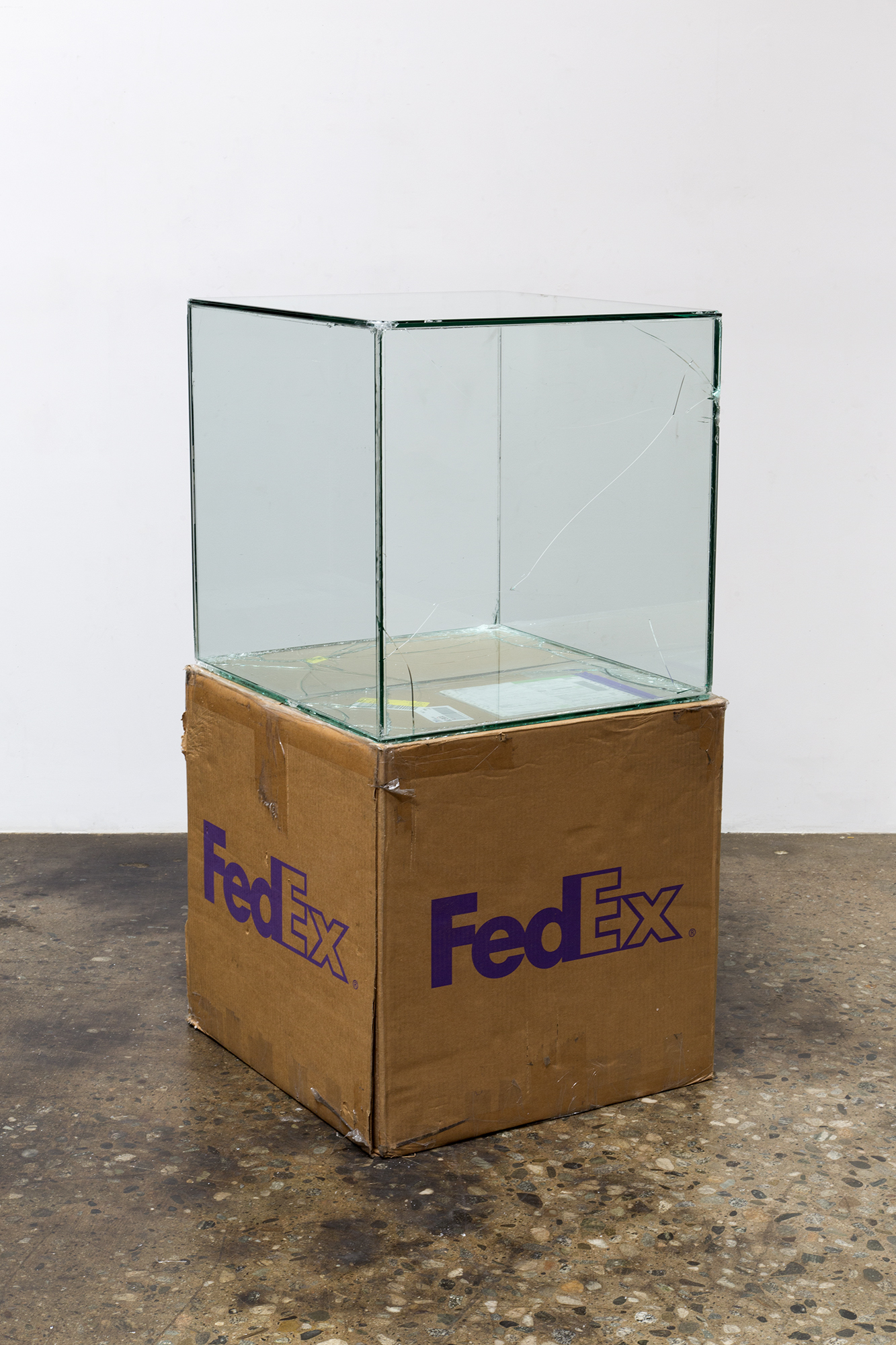 FedEx® Large Kraft Box  © 2008 FEDEX 330510 REV 6/08 GP, International Priority, Los Angeles–Tokyo trk#778608512056, March 9–13, 2017    2017–   Laminated glass, FedEx shipping box, accrued FedEx shipping and tracking labels, silicone, metal, tape  24 x 24 x 24 inches   Transparencies, 2017