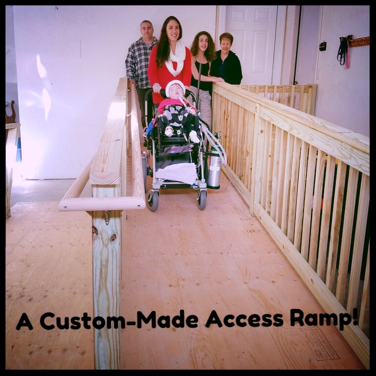 Leila and her family posing on their new access ramp provided by Holton's Heroes.