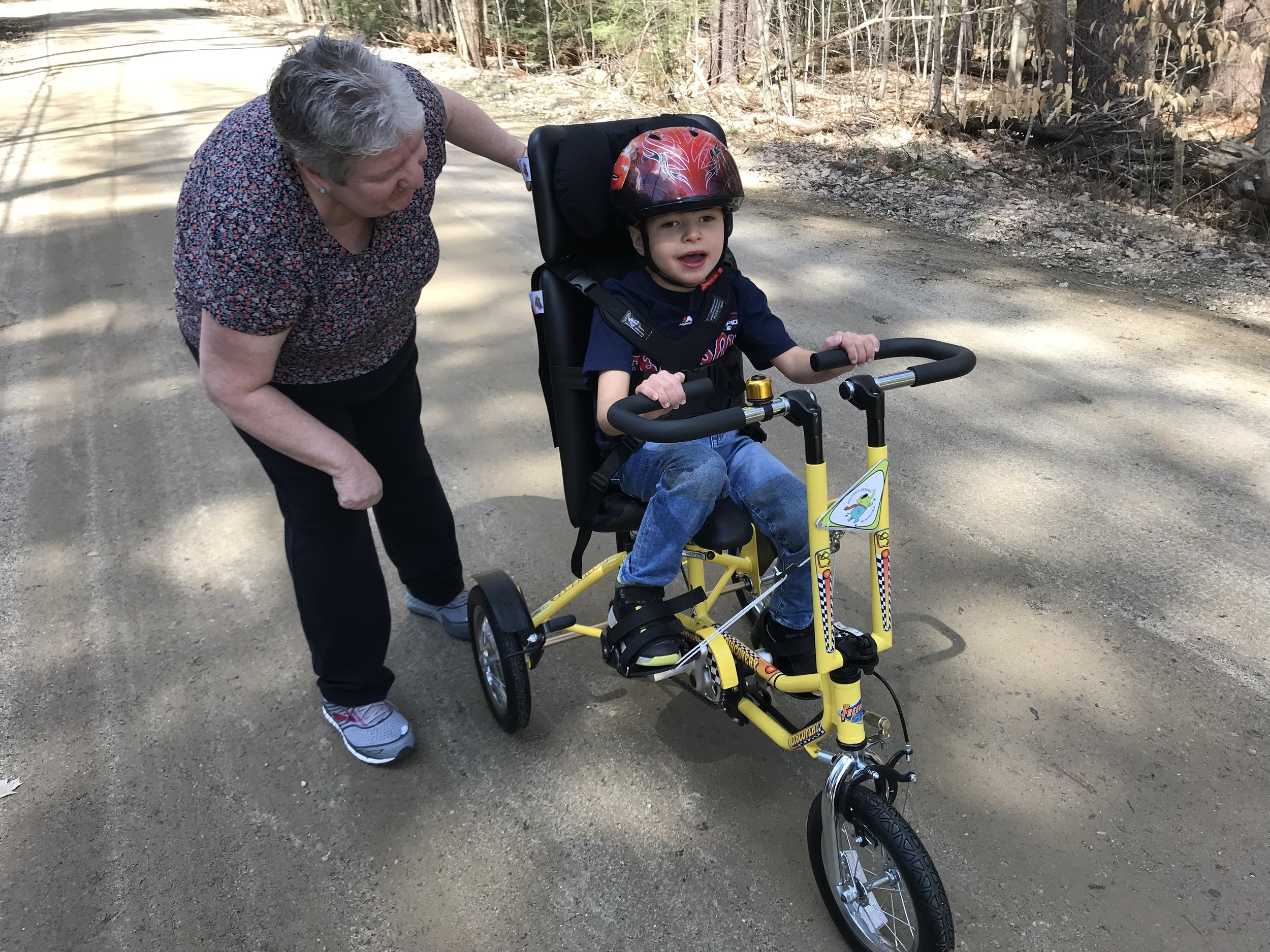 Laurie cheers on Noah as he peddles his new Freedom Concepts bike