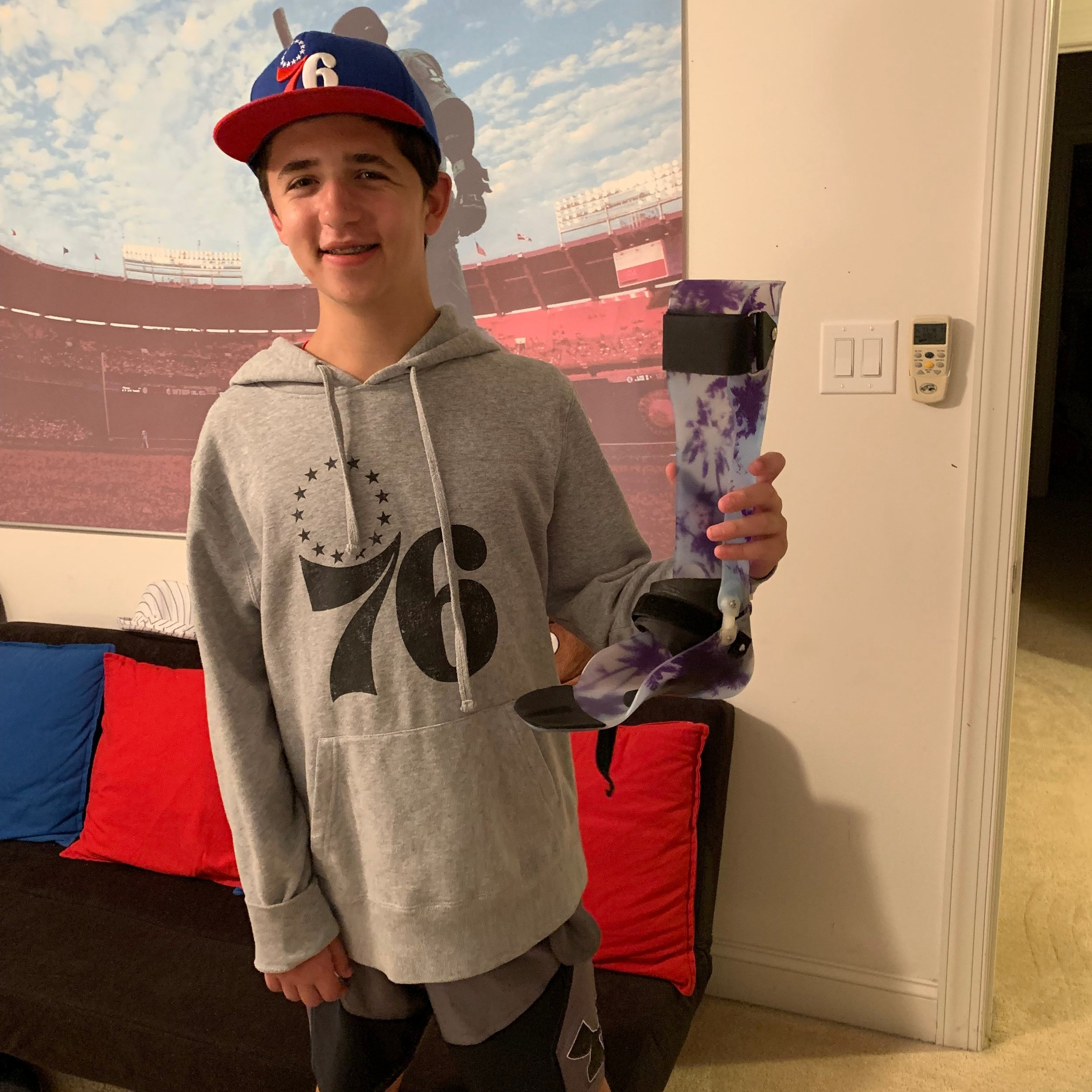 Chase holds up his brand new leg brace Holton's Heroes was able to purchase thanks in large part to all of our donors.