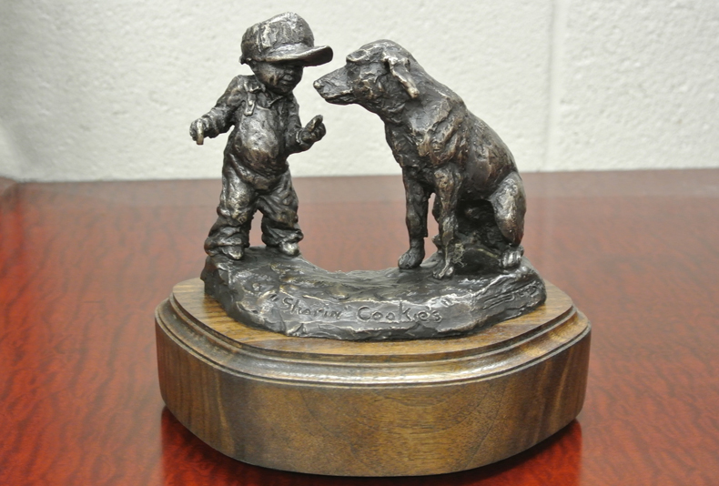 Sharin' Cookies  A small bronze sculpture about a boy and his dog, sharin' cookies.