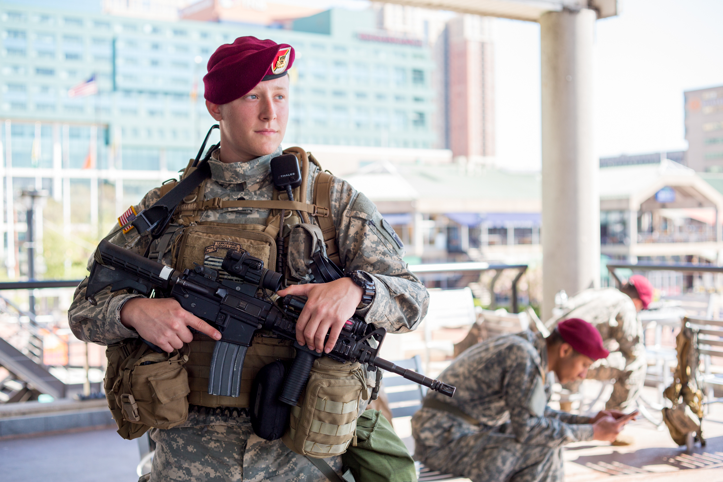 Ian McKinley, specialist, 21, stands guard at The Inner Harbor in Baltimore, Maryland, which has since become a staging area for the National Guard.