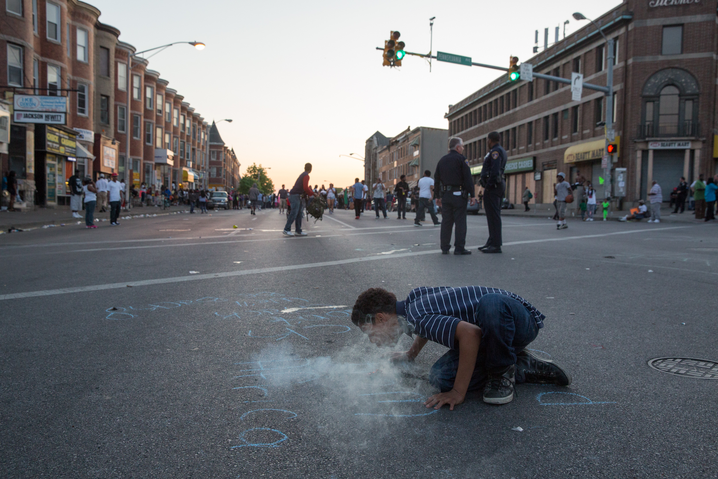 A young boy kindles incense in front of the Pennsylvania and North Avenue CVS which has since become a gathering point for protestors. In the background, police officers look on as a block party to celebrate the indictment of the officers who allegedly murdered Freddie Gray. Baltimore, Maryland.
