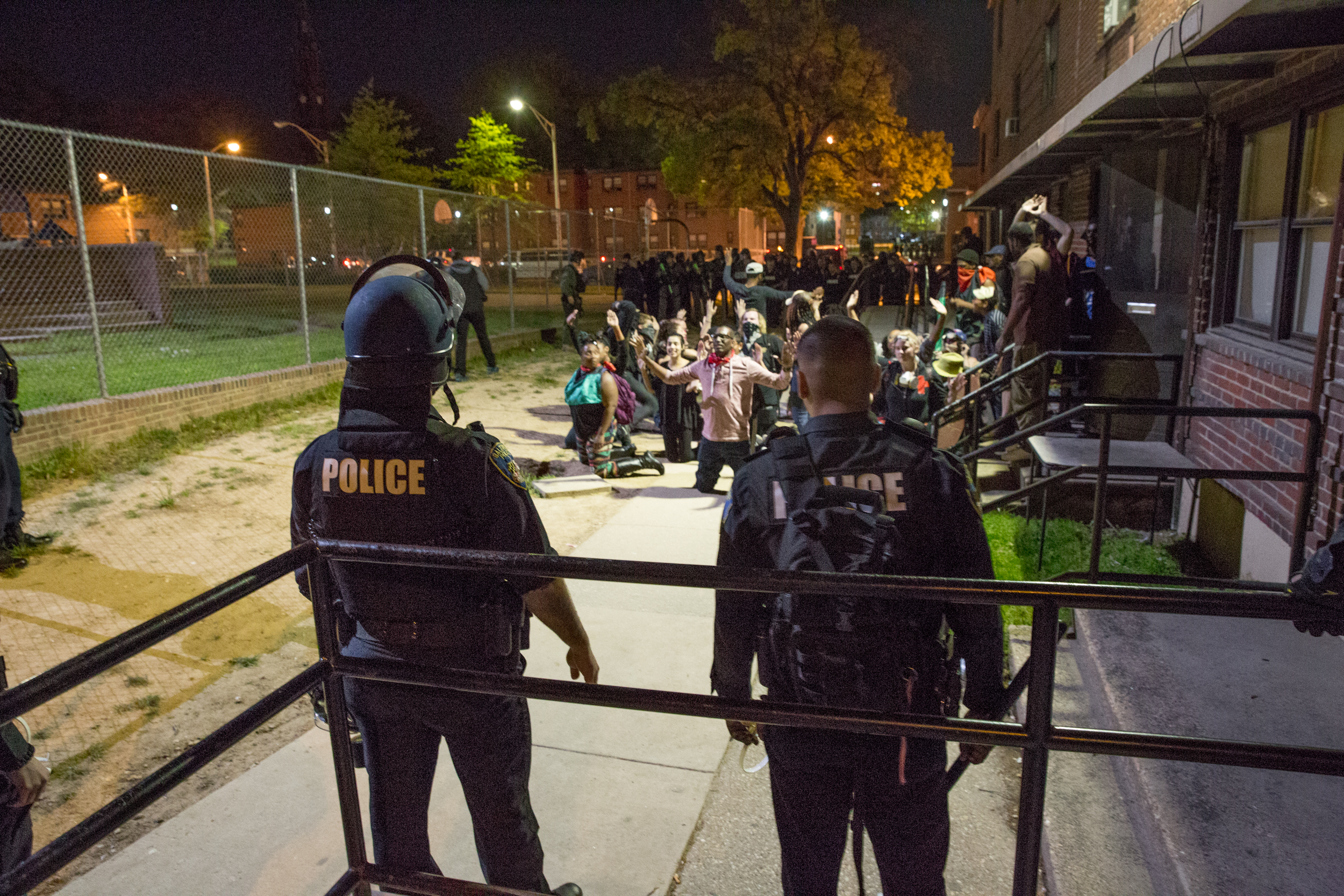 Police corner protestors post-curfew in a Greenmount housing project in Baltimore, Maryland.
