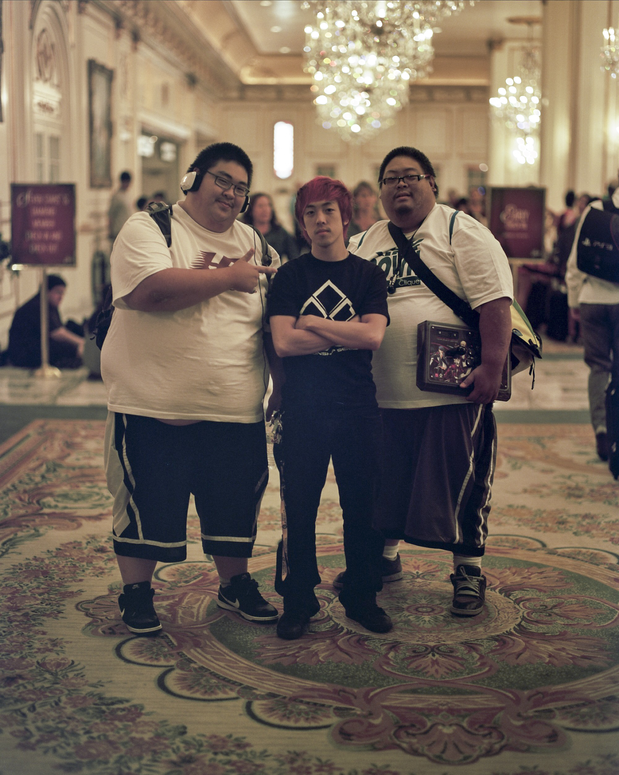 Two sponsors proudly pose with the player they helped support to compete at the EVO competitive gaming tournament at the Paris Hotel, in Las Vegas, Nevada