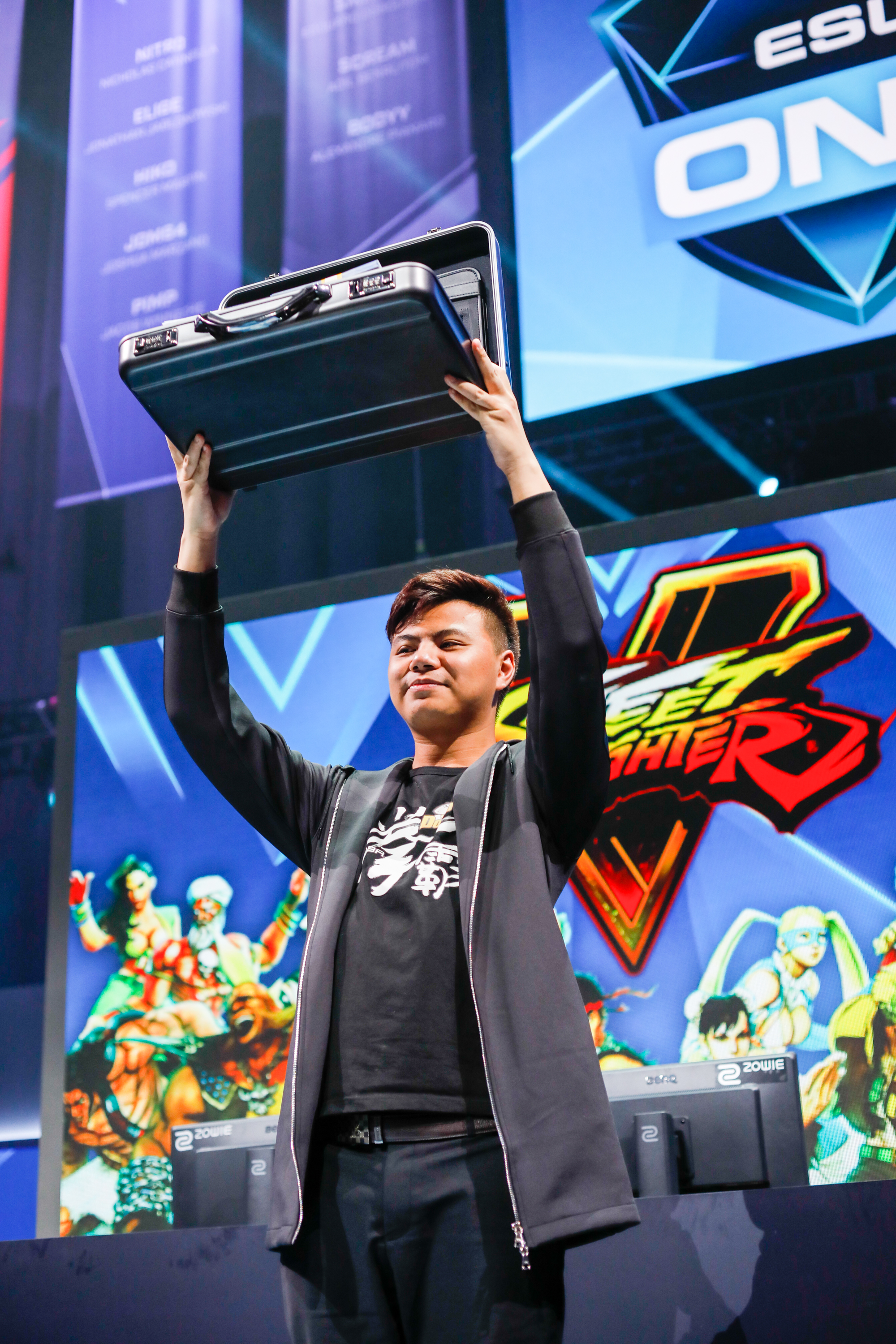 "Zhuojun ""Xiao Hai"" Zeng holds up his prize: a briefcase filled with $30,000.00 cash, the Street Fighter V logo and ESL branding are visible behind him."