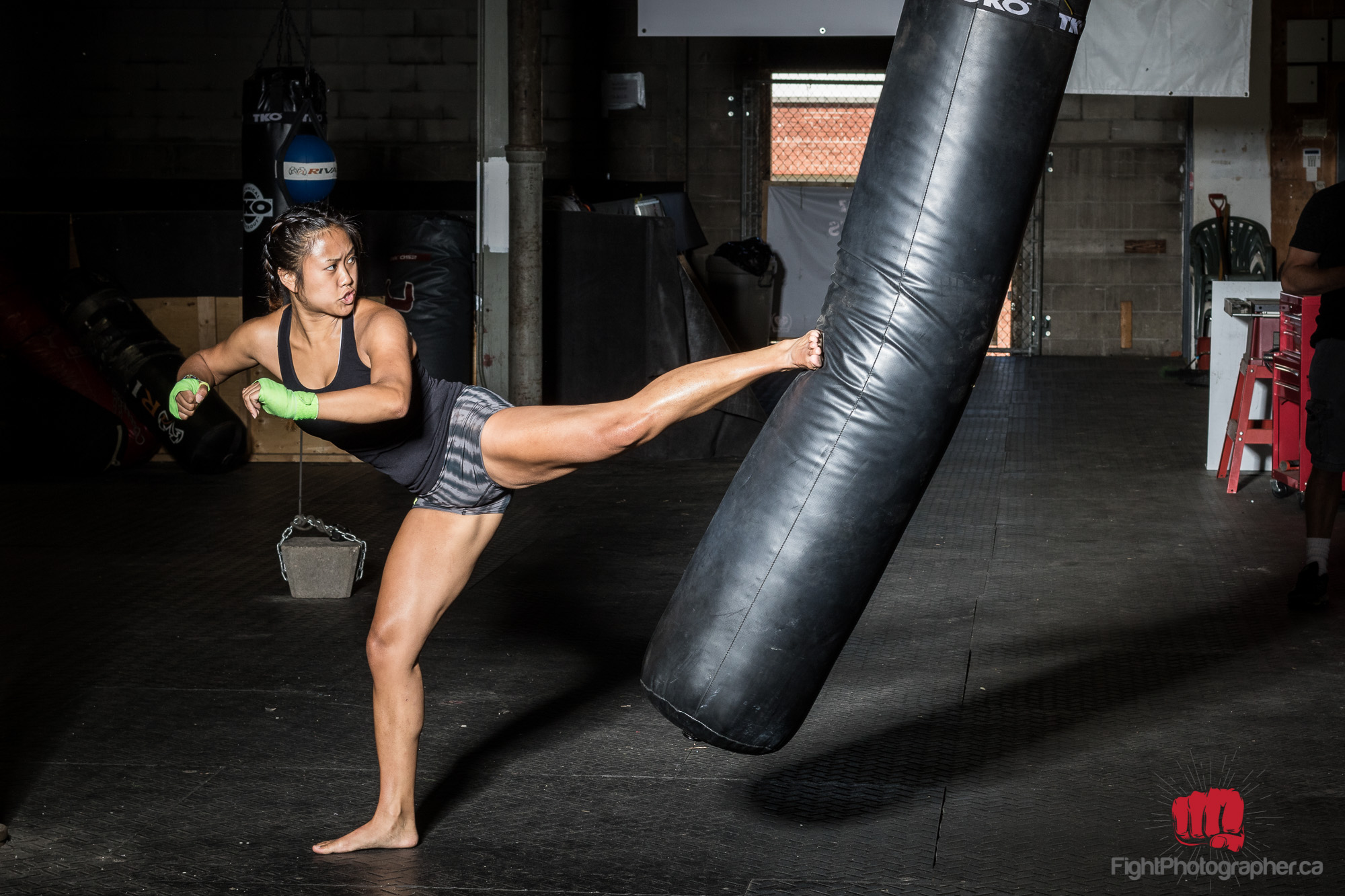 woman karate bends heavybag