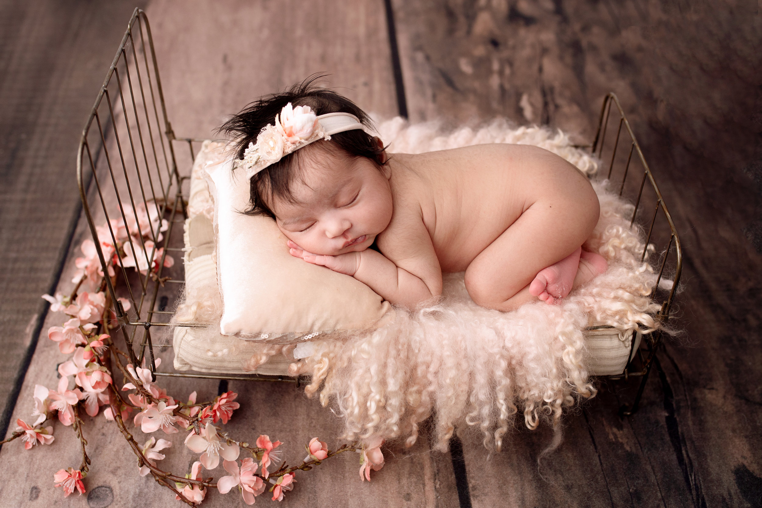 newborn baby on little bed with flowers