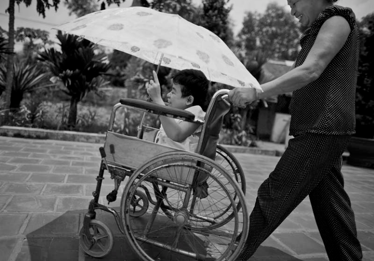 Thao is being pushed in her wheelchair by her mother. The family wheels Thao out to the separate structure that houses Thao's library along with her father's pig feed and fertilizer. There Thao will sit in her library for a majority of the day excepting local children from the village.