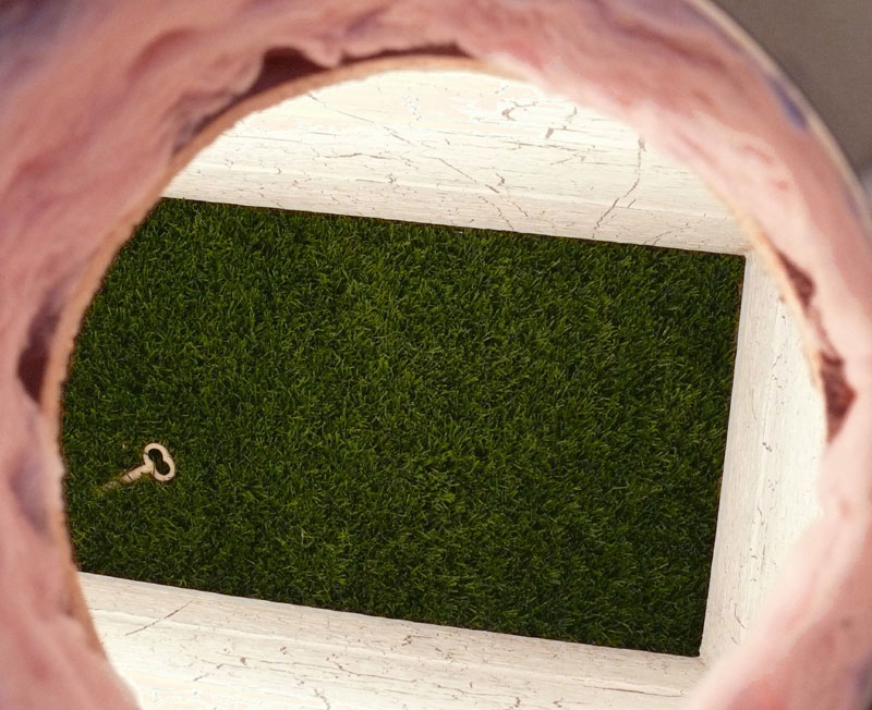"""""""Whitewash (interior view)"""" (2008)<br> Wood, sheetrock, paint, insulation, synthetic turf, incandescent light, graphite, <br> 45 x 24 x 19.5 inches."""