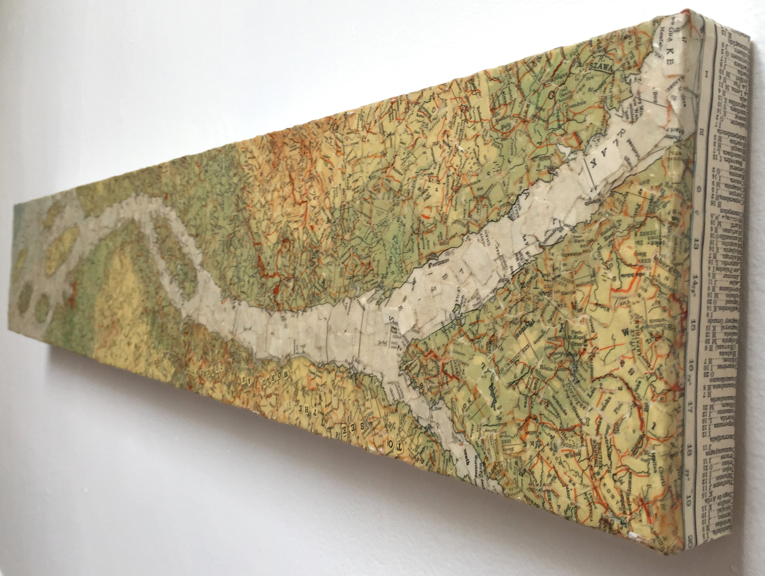 """To See the World..."" (2009)<br>Torn map collage on canvas, 6 x 36 x 2 in."