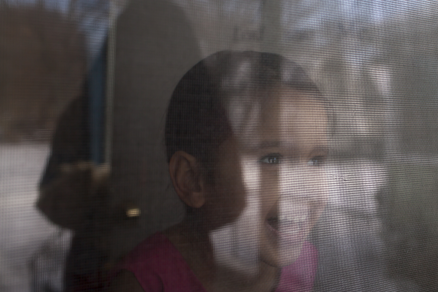 Yarieliz Flores, 3, surprises her mom, Jenismat Flores, 26, through the screen door, Rochester, N.Y., Mar. 22, 2015.