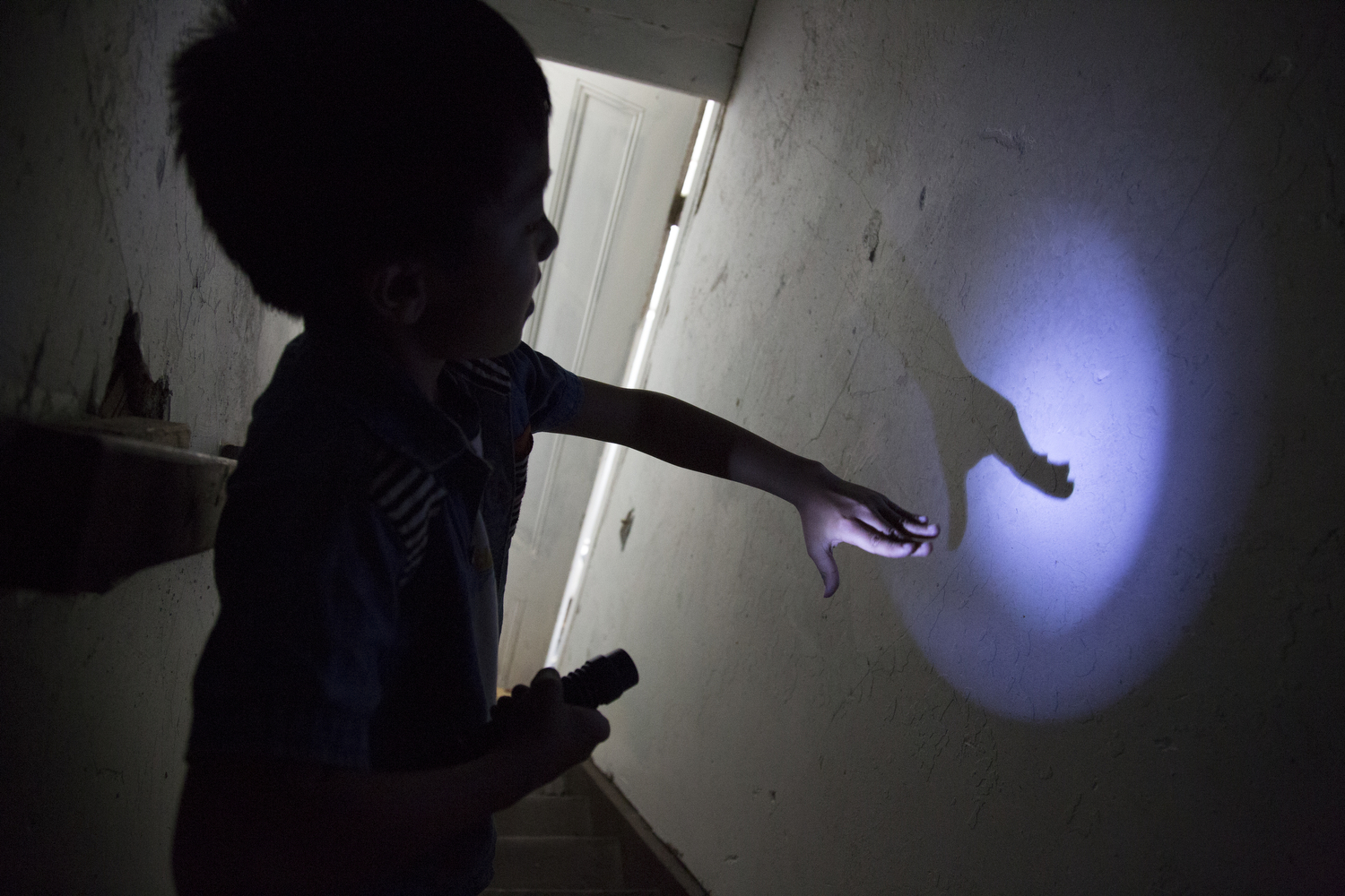 "Subash Rai, 10, experiments with light and shadow on his way down the attic stairwell, Rochester, N.Y., May 16, 2015. Subash said, ""I would like to create a science lab in the attic."""