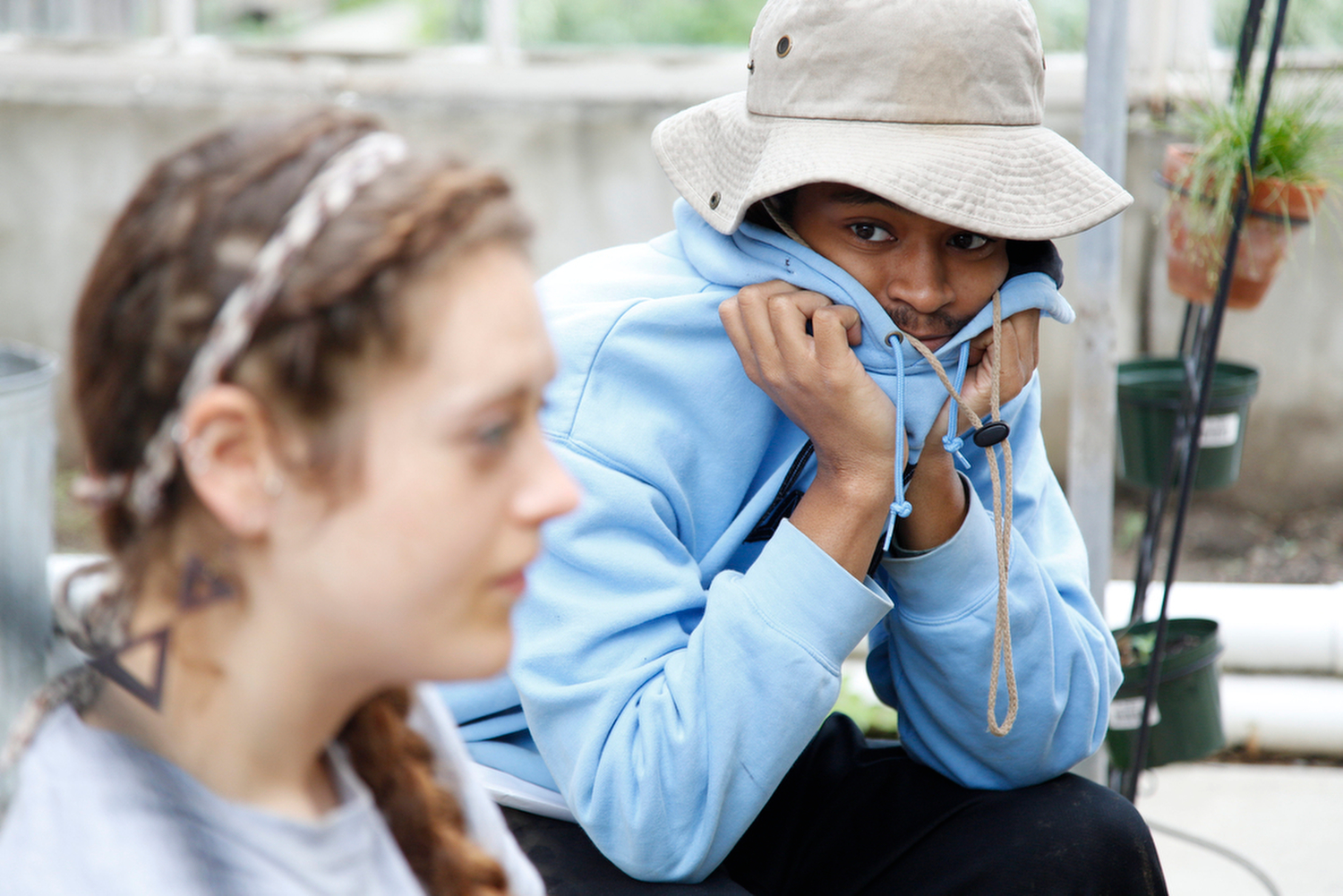Jarvis DuVal, 18, listens to Rachel Farley, 25, while she shares during the afternoon check-in at the Seedfolk City Farm, Rochester, N.Y., June 8, 2015.