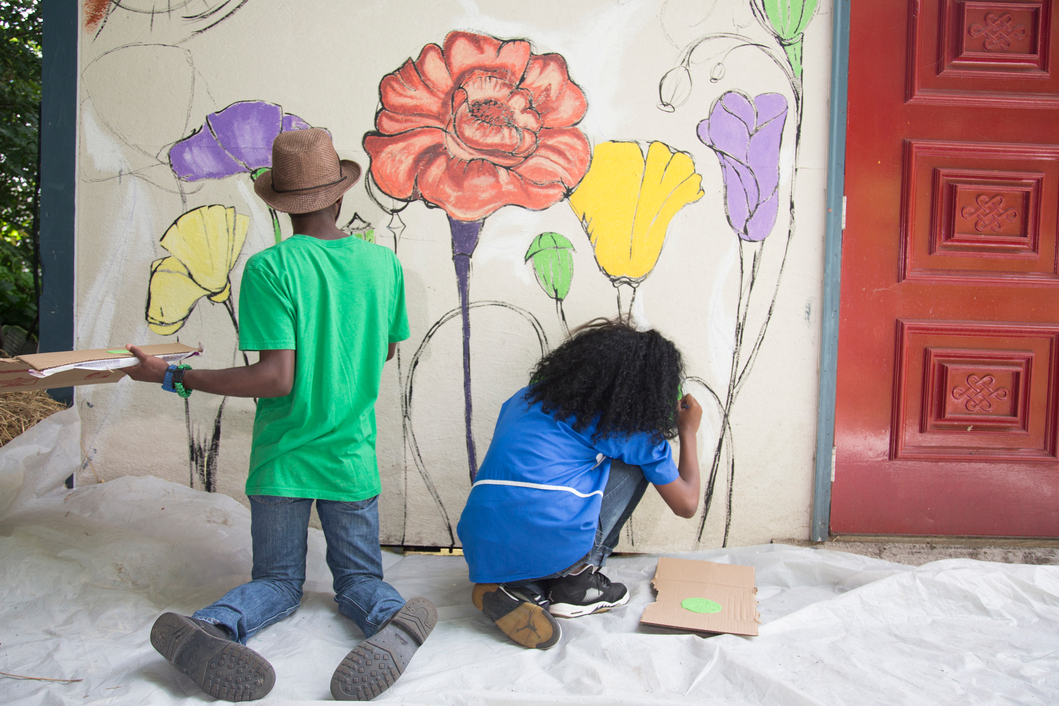 "Kasim Wallace, 17, (L) and Eugenia Taylor (R ) paint the mural on the shed at the Seedfolk City Farm during the Summer Program at the Greenhouse, Rochester, N.Y., Aug. 7, 2015. Kasim said, ""This is the most fun thing ever."""