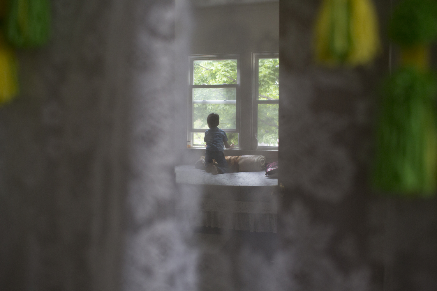 Subash Rai, 10, looks out the window of the upstairs bedroom of his house awaiting his next adventure, Rochester, N.Y., May 16, 2016.