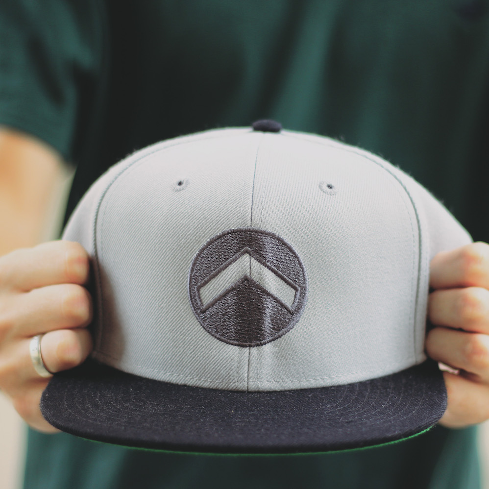 Snapback Cap - Embroidered logo on front.