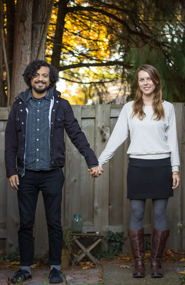 Couple standing in hipster pose outside smiling and looking at the camera.