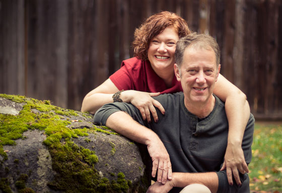 Couple smiling at the camera with arms draped over the other outside by a large mossy rock.
