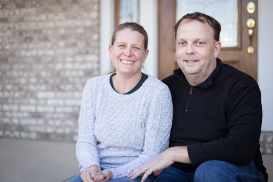 Couple smiling at camera and sitting on a front porch.